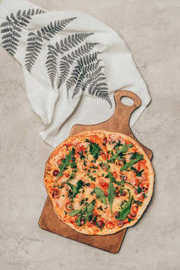 Delicious pizza on wooden cutting board with napkin on light background