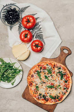 Delicious pizza on wooden cutting board and recipe ingredients on light background
