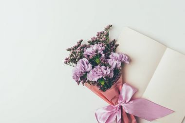 beautiful elegant bouquet of tender purple flowers and blank greeting card isolated on grey