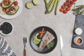 pohled shora na rybí filé s baby karotkou na desku a čerstvou zdravou zeleninu a ovoce na grey