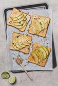 zdravé sendviče s plátky jablko, limetkou a medem naběračka na grey