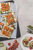 pohled shora na zdravé sendviče s baby karotkou a rukolou na grey