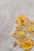 Fotografie pohled shora zdravé sendviče s plátky jablko a pomeranč a med naběračka na grey