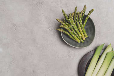 top view of fresh organic asparagus and leeks on plates on grey