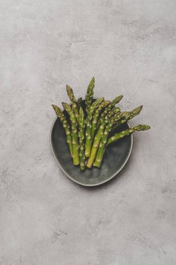 top view of fresh healthy asparagus on plate on grey