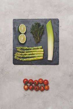top view of tomatoes, lime, leek and asparagus on slate board on grey
