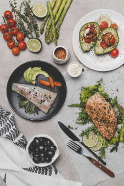 top view of healthy dishes with fish, meat and avocado on grey