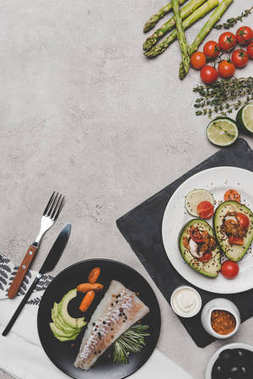 top view of delicious healthy dishes with fish and avocado on grey