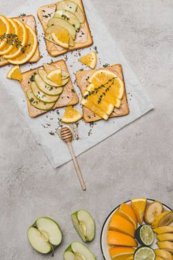 top view of healthy sandwiches with fresh fruits and honey dipper on grey