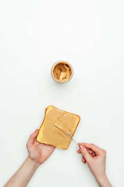 cropped image of woman putting peanut butter on bread isolated on white