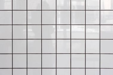 Wall of white glossy tiles with reflection