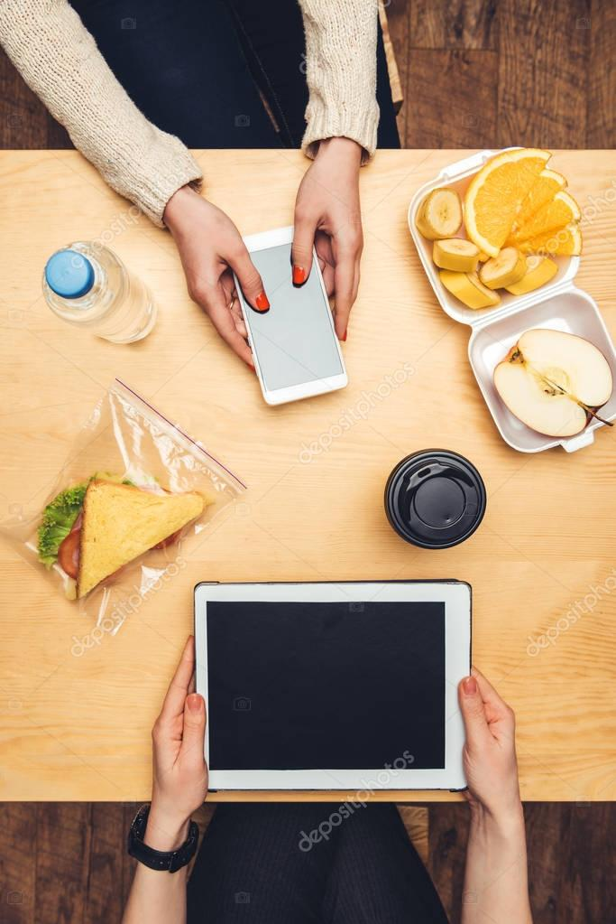 Cropped image of women sitting at table with take away food and using gadgets