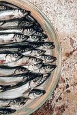 Oříznout obrázek hromadu ryb na talíři na rustikální povrch
