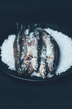 Close up of pile of salted fish in frying pan isolated on black