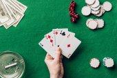 Fotografia Mano femminile che tiene le carte da gioco da tavolo del casinò