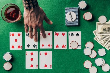 Man choosing cards by whiskey on casino table