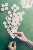 Mužské ruky s kartami poker casino tabulce