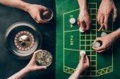 Ruka s whisky a čipy kasino tabulky s sázky a ruleta