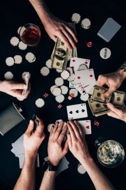 People playing poker by casino table with money and chips