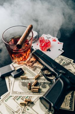 Gun and bullets on casino table with money and gambling objects
