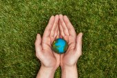 Photo cropped image of man holding earth model in hands above green grass, earth day concept