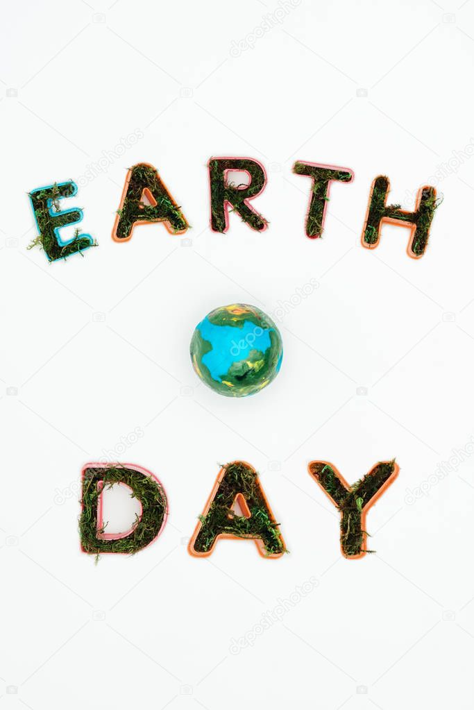 top view of earth model with text earth day isolated on white