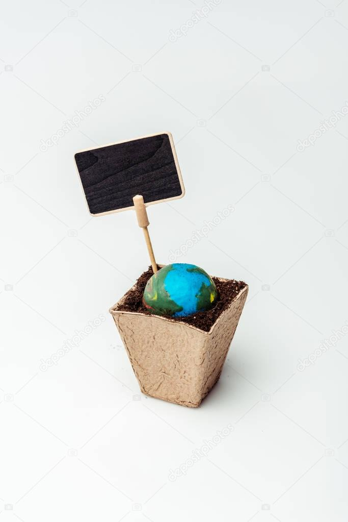 earth model in flower pot with soil and blackboard isolated on white, earth day concept