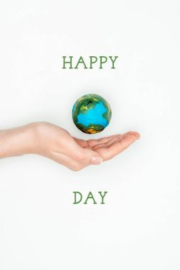 cropped image of woman holding earth model on hand with sign happy earth day isolated on white