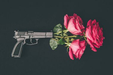 Bouquet of red roses shooting from gun isolated on black