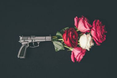 Gun shooting with bouquet of rose flowers isolated on black