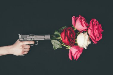 Female hand holding gun with bouquet of rose flowers isolated on black