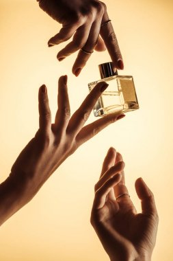 cropped view of female hands with perfume, isolated on yellow