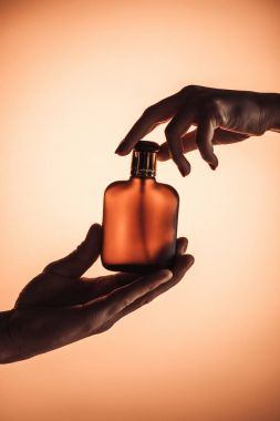 cropped view of man and woman holding one bottle of perfume, isolated on orange
