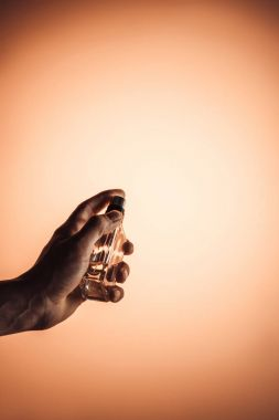 cropped view of man holding spray bottle of perfume, isolated on orange