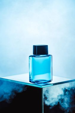 one blue bottle with mens perfume, on blue