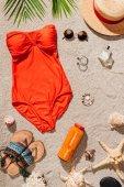 felülnézete homokos tengerparton elegáns piros fürdőruha-es többféle tartozékkal