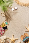 Photo top view of stylish female accessories lying on sandy beach