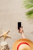 Fotografie oříznutý snímek žena v klobouku pomocí smartphone, zatímco leží na písečné pláži