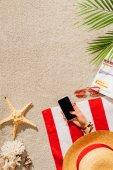 levágott lövés nő használ smartphone, pihenve, homokos strandon