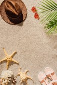 top view of stylish straw hat with sunglasses and sandals on sandy beach
