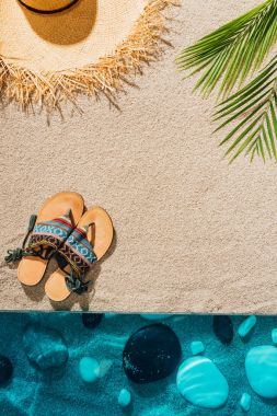 top view of stylish flip flops and straw hat on sandy beach