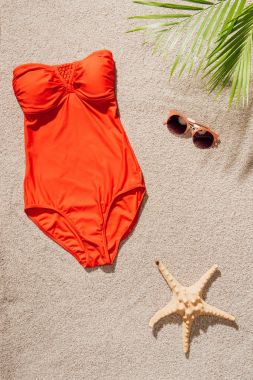 top view of stylish red swimsuit and sunglasses lying on sandy beach