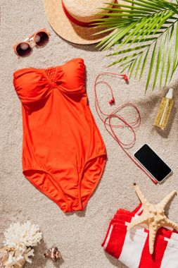 Top view of stylish red swimsuit with smartphone and accessories lying on sandy beach stock vector
