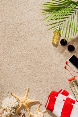 top view of striped towel with various objects lying on sandy beach