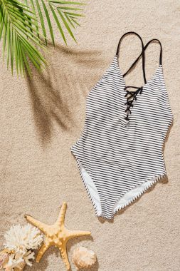 top view of stylish swimsuit lying on sandy beach
