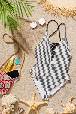 top view of swimsuit and accessories lying on sandy beach