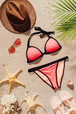 top view of stylish bikini lying on sandy beach with accessories