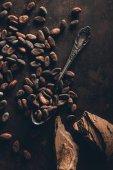 Draufsicht der Kakaobohnen, Vintage Löffel und Schokoladenstücke auf dunkle Oberfläche