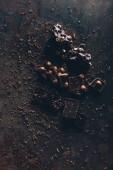 pohled shora lahodné různé kousky čokolády s ořechy na tmavý podklad