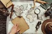 partial view of male hand, map, blank burnt paper, watch, magnifying glass, compass and hat on wooden surface